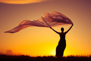 Woman outdoors wearing dress holding a long fabric blowing in the wind. Freedom and serenity concept.