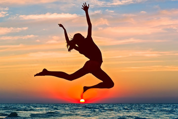 Silhouette of a girl jumping over the sea at sunset