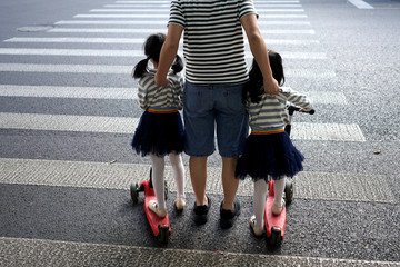 A father crosses a road with his twin daughters in Shanghai