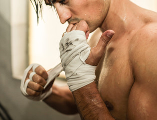 MMA fighter wrapping is hands getting ready to fight.