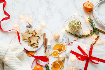 Christmas atmoshpere flatlay. Overhead view. Gingerbread cookies, tangerines and new year decorations on marble background