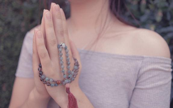 Woman Praying with Mala