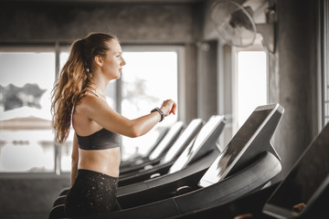 Fit young woman caucasian running on machine treadmill workout in gym. Glad smiling girl is enjoy with her training process. Concept of fitness, healthy life, Sport, Lifestyle.