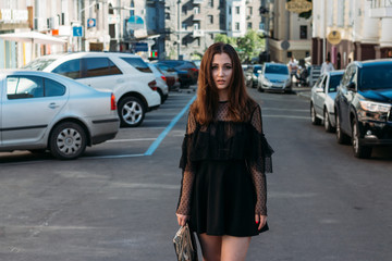 Emotional portrait of Fashion stylish portrait of pretty young woman. city portrait. sad girl. brunette in a black dress. expectation. dreams