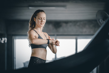 Fit young woman caucasian running on machine treadmill and looking smart watch workout in gym. Glad smiling girl is enjoy with her training process. Concept of fitness, healthy life, Sport, Lifestyle.