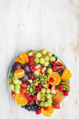 Wall Mural - Healthy fruit platter, strawberries raspberries oranges plums apples kiwis grapes blueberries on the white wooden table, top view, copy space for text, vertical, selective focus
