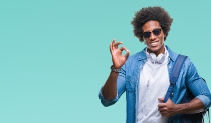 Afro american man wearing headphones and backpack over isolated background doing ok sign with fingers, excellent symbol