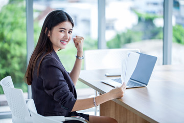 beautiful asian young business woman raised hands celebrating to success achieving goals and hand holding paper document file with laptop computer on desk in office. girl excited arms up in  Workplace