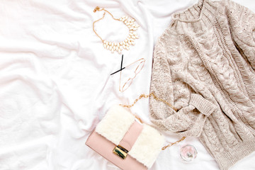 Wall Mural - Woman clothes and accessories set on white background. Women's warm sweater, bag, glasses. Modern and casual outfit. Shopping concept. Flat lay, top view.