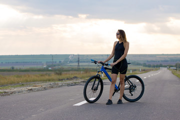 Girl on a mountain bike on offroad, beautiful portrait of a cyclist at sunset