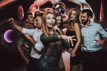 Solo. Trendy Nightclub. Woman in Green. Dress.