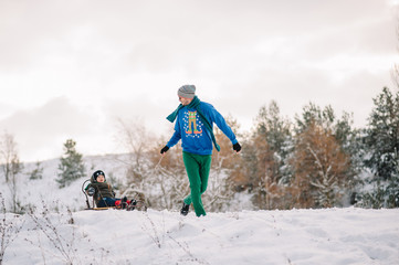 A father is carrying a child on a sled. Father walks with her son over the snow-covered forest. Cheerful winter vacation. Winter fun. Baby on the sleigh.