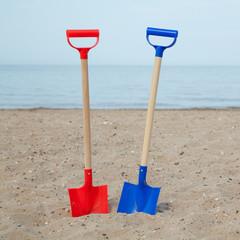 Zwei Spielzeugschaufeln am Strand