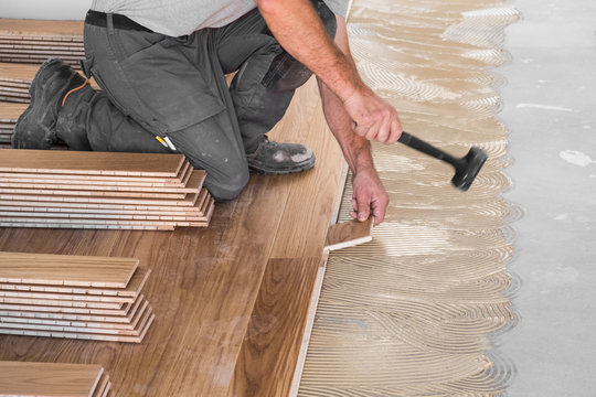 Worker installing wooden flooring boards on applied adhesive