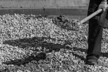 black and white picture of construction worker holding showel with gravel