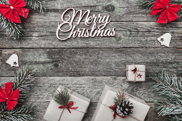 Upper, top, view from above of winter figurines, evergreen branch, present boxes and red Merry Christmas inscription on gray background, with space for text writing, greeting.