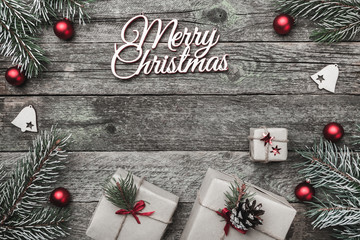 Upper, top, view from above of white winter figurines, evergreen branch, red toys, presents and Merry Christmas inscription on gray background, with space for text writing, greeting