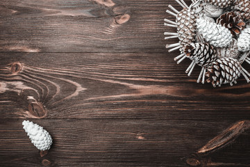 Brown wood background with texture. Decorative fir cones. Fellowship, New Year and Xmas. Space for Santa's message and holidays. Holiday card. Xmas and Happy New Year composition. Flat lay, top view