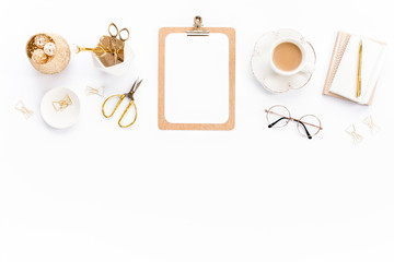 Home office workspace with clipboard, notepad and golden accessories on white background. Flat lay, top view