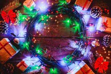 Wooden background with colored lights and stars. surrounded by gifts and cones. In the center there is space for the holiday message. Top view.