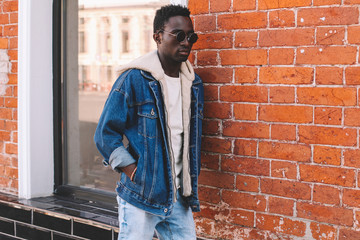 Wall Mural - Fashion african man wearing jeans jacket poses on city street, brick wall background
