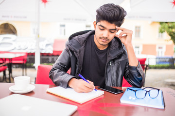 Young indian man freelancer of creative occupation writing down in copybook, noting goals, achievements and failures in time management check list during coffee break at cafe table