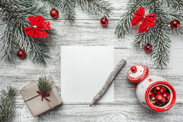An upper view of a Christmas, new year letter, card writing, on a rustic background, with old style pencil, tea pot and evergreen, snowflake, ribbon, paper present ornaments
