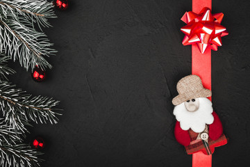 Upper top view of a red ribbon, present, handmade Santa toy and evergreen branch on a stone black background, with space for text writing