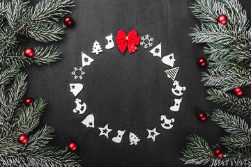 Upper, top, view from above, of handmade wooden toys circle, round shape, red bow evergreen branches on black background, with space for text writing, greeting.