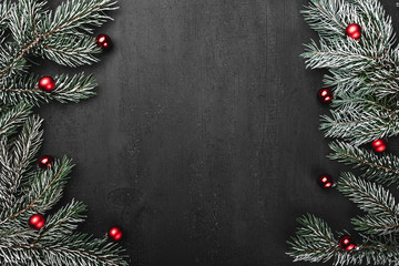 Upper, top, view from above, evergreen branches, tree globes on black background, with space for text writing, greeting.