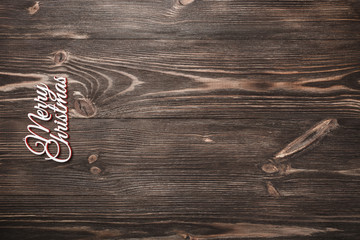 View from above of a Merry Christmas inscription on wooden background, greeting card with space for text writing