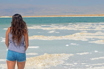 long-haired brunette walks the islands from salt in the dead sea, Israel