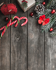 Christmas theme with fir branches, red bows and globes, cones, present boxes, cookies and candies, on rustic dark wooden background viewed from above, top, greeting card with space for text