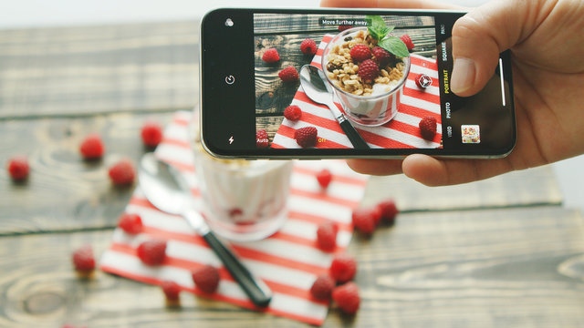 Hand of anonymous person holding modern smartphone and making lovely photo of delicious fruit dessert and spoon on wooden table