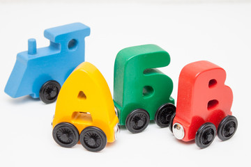 Russian wooden letters train alphabet with locomotive. Bright colors of red yellow green and blue on a white background. Early childhood education, learning to read, preschool and kids game concept.