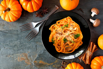 Pasta with a pumpkin, mushroom cream sauce. Autumn meal. Top view table scene on a dark background with copy space.