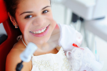 Beautiful smile with white teeth. A dentist examines the oral cavity of a young beautiful girl through a magnifying glass in the dental office.