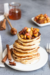 Stack of delicious sweet and spicy apple pancakes with fried caramelized apples, anise, cinnamon and honey on a white plate. Autumn breakfast. Copy space.