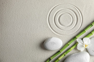 Photo sur Plexiglas Zen pierres a sable Bamboo branches with spa stones and orchid on sand, top view. Space for text