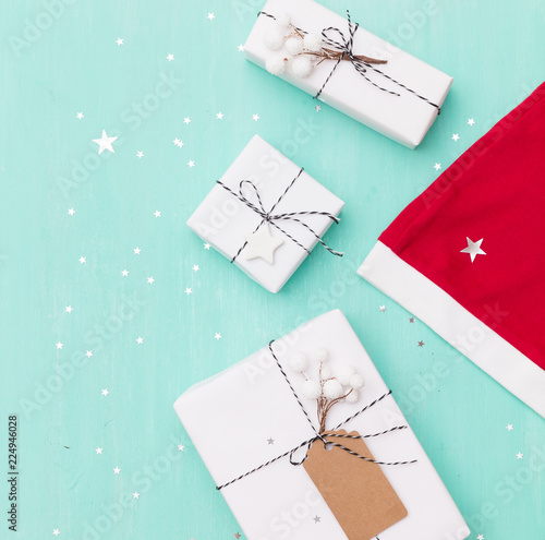 closeup of nice christmas gifts wrapped in white paper christmas tree decorations santas hat - Nice Christmas Gifts