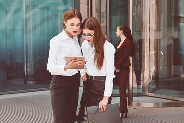 Business lady. Office staff. Two young girls with electronic tablets communicate against the background of a office building and a group of people. Electronic Gadget. Five people. 5.