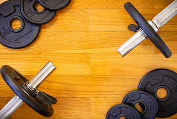 Dumbell Bars and Weights on Wooden Background