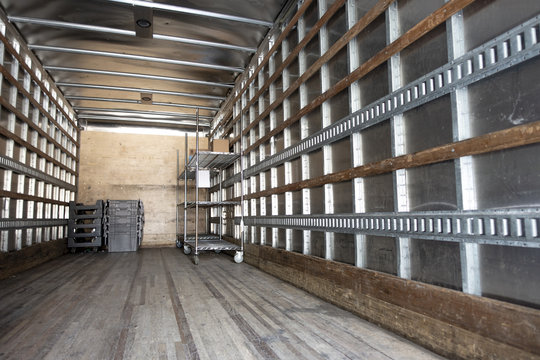 Inside an industrial shipping truck's cabin empty with a few things and crates mtal and wood