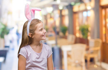Young beautiful girl wearing easter bunny ears over isolated background looking away to side with smile on face, natural expression. Laughing confident.