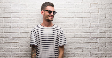 Young adult man wearing sunglasses standing over white brick wall looking away to side with smile on face, natural expression. Laughing confident.