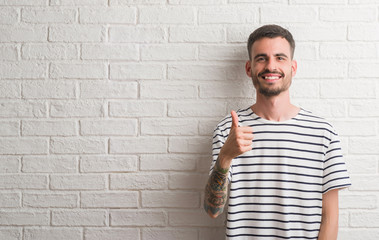 Young adult man standing over white brick wall happy with big smile doing ok sign, thumb up with fingers, excellent sign