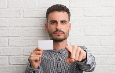 Young adult man over brick wall holding blank card pointing with finger to the camera and to you, hand sign, positive and confident gesture from the front