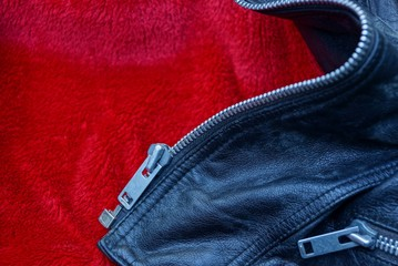 gray metal zip on a piece of leather clothes on red cloth