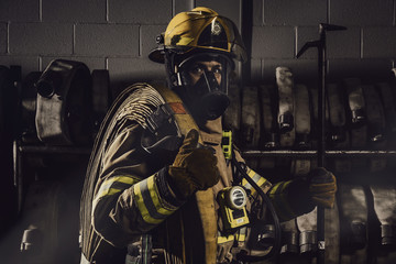Firefighter wearing the protection clothes holding fire hose
