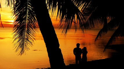 Silhouette of couple taking photos of the sunset